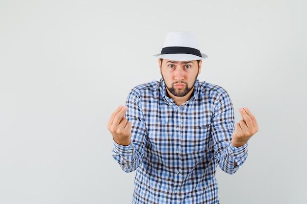 Młody mężczyzna w koszuli w kratę, kapeluszu, próbuje coś wyjaśnić i wygląda poważnie, widok z przodu.