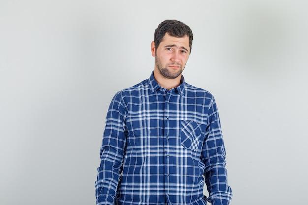Młody mężczyzna w koszuli w kratę marszczy brwi, jakby zamierzał płakać i wyglądał na zdenerwowanego