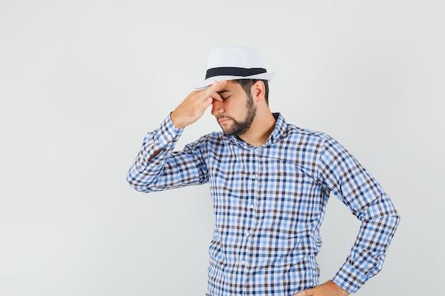 Młody mężczyzna w koszuli w kratę, z kapeluszem przecierającym oczy i nos, wyglądającym na zmęczonego, widok z przodu.