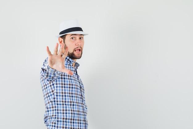 Młody mężczyzna w koszuli w kratkę, kapelusz pokazujący gest stop i wyglądający na wzburzonego.