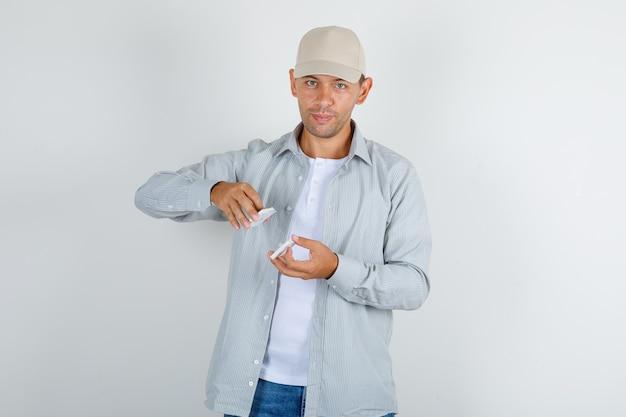 Młody mężczyzna w koszuli z czapką trzymając karty do gry i uśmiechnięty