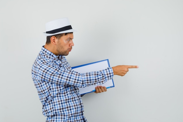 Młody mężczyzna w kraciastej koszuli i kapeluszu wskazującym na bok
