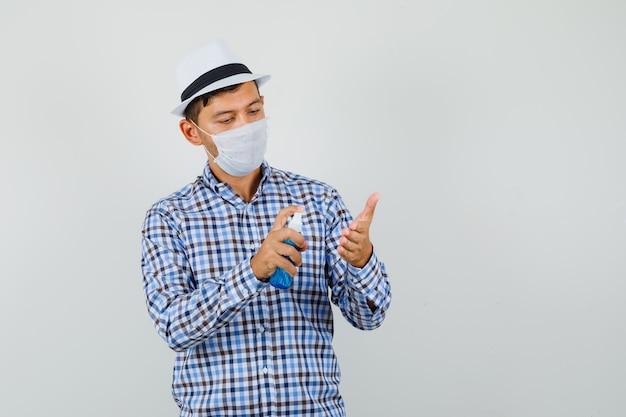 Młody mężczyzna w kraciastej koszuli, kapeluszu, masce, nakłada na rękę spray dezynfekujący i patrzy uważnie