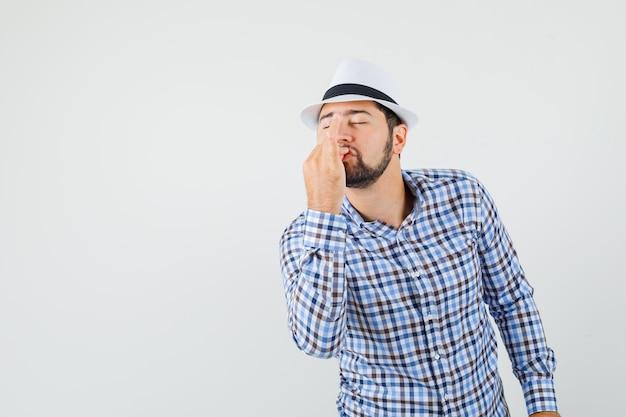 Młody mężczyzna w kraciastej koszuli, kapeluszu pokazującym pyszny gest i wyglądającym na zachwyconego, widok z przodu.