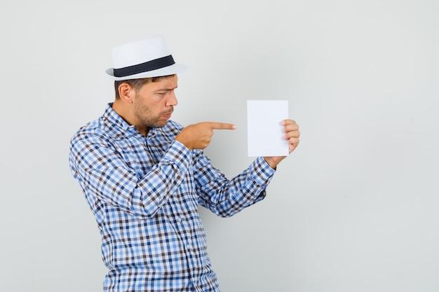 Młody mężczyzna w kraciastej koszuli, kapeluszu, wskazując na kartkę papieru i patrząc skupiony