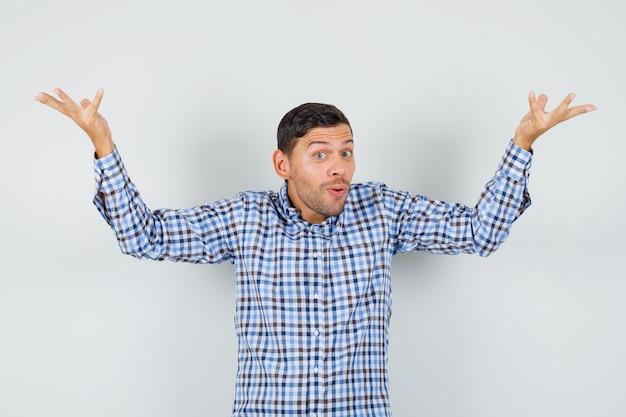Młody mężczyzna w kraciastej koszuli podnosi dłonie w zdziwionym geście i wygląda optymistycznie