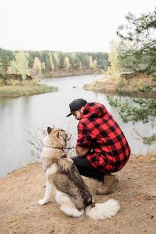 Młody mężczyzna w kraciastej kurtce i czarnych dżinsach siedzi na przysiadach przez uroczego rasowego zwierzaka, jednocześnie odpoczywając nad jeziorem w lesie