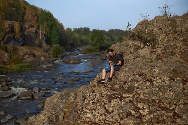 Młody mężczyzna w krótkich spodenkach i koszulce siedzi na skałach nad górską rzeką i gra na ukulele high q...