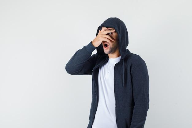 Młody mężczyzna w kurtce, koszulce, patrząc przez palce i wyglądający na przestraszonego, widok z przodu.