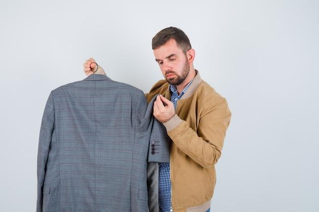 Młody mężczyzna w marynarce, koszuli patrzy na garnitury, stoi bokiem i wygląda na zdziwionego.