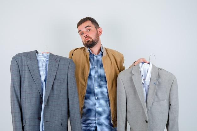 Młody mężczyzna w marynarce, koszuli zdziwiony wyborem garnituru i zamyślonym spojrzeniem z przodu.