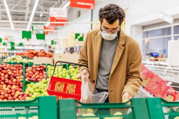 Młody mężczyzna w masce medycznej wybiera owoce w dużym supermarkecie. środki ostrożności podczas pandemii koronawirusa. zdrowe odżywianie.