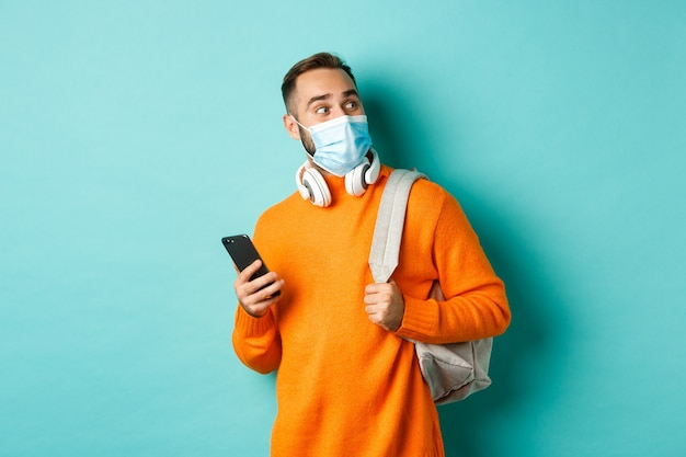 Młody mężczyzna w masce na twarz, używający telefonu komórkowego, trzymający plecak, patrzący w prawo zdumiony, stojący na jasnoniebieskim tle.