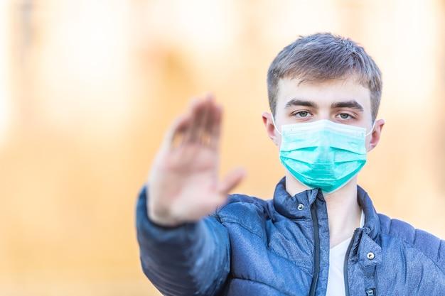 Młody mężczyzna w masce ochronnej pokazujący gest - stop koronawirusa covid-19.