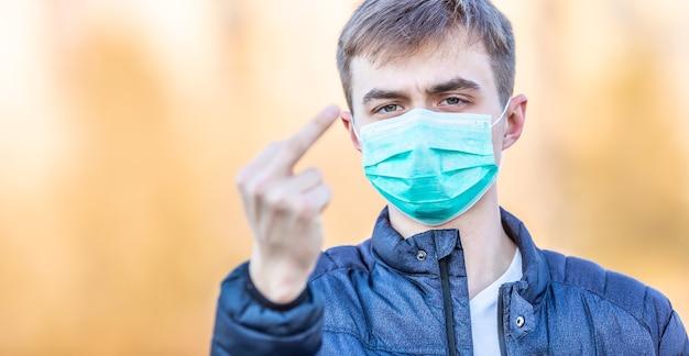 Młody mężczyzna w masce ochronnej pokazuje nieprzyzwoity gest - skurwiel. koncepcja koronawirusa covid-19.