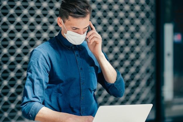 Młody mężczyzna w masce ochronnej rozmawia przez telefon