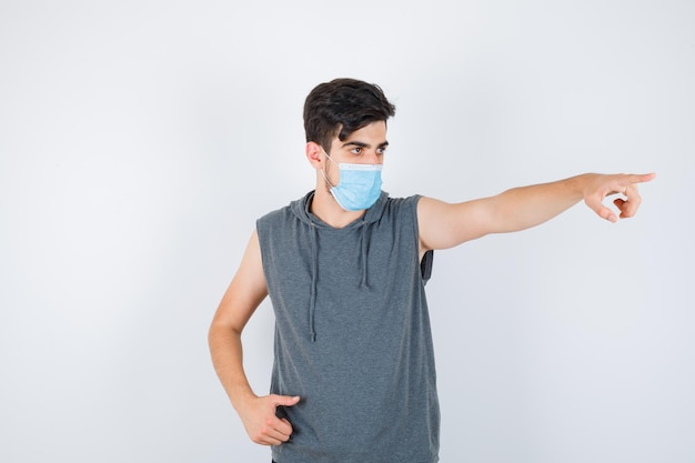 Młody mężczyzna w masce, pokazując kciuk do góry i wskazujący w prawo w szarym t-shircie i wyglądający poważnie