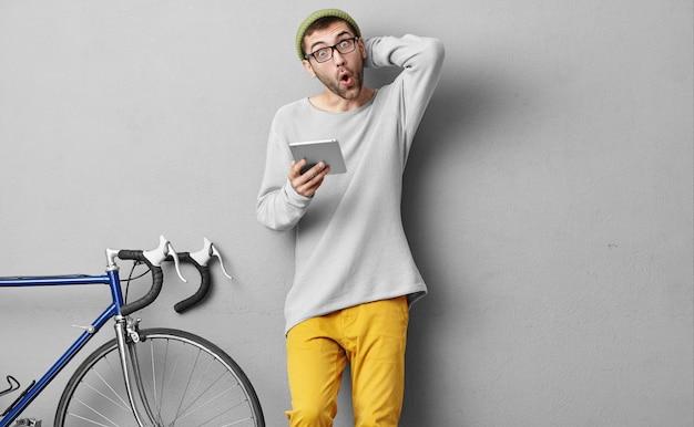 Młody mężczyzna w modnych ciuchach, robiąc zakupy online, używając tabletu, jest zaskoczony
