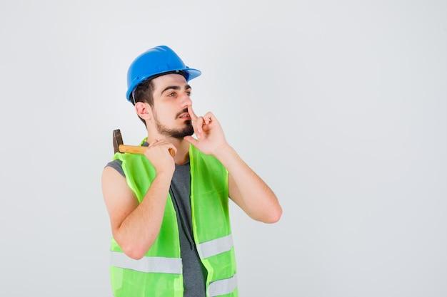 Młody mężczyzna w mundurze budowlanym podnosi topór przez ramię i pokazuje gest ciszy i wygląda na skupionego