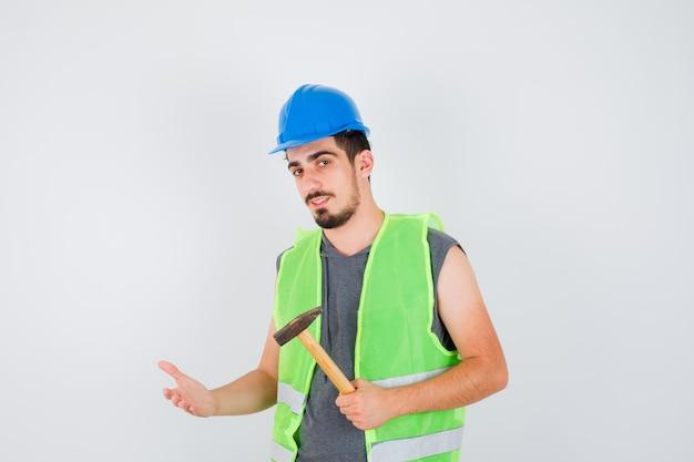 Młody mężczyzna w mundurze budowlanym trzyma siekierę i wyciąga rękę w jej kierunku i wygląda na szczęśliwego
