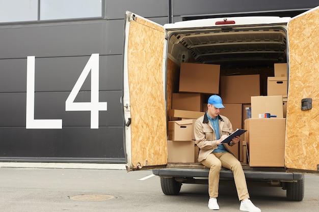Młody mężczyzna w mundurze wypełniania dokumentów siedząc na furgonetce pracuje w dostawie ładunku