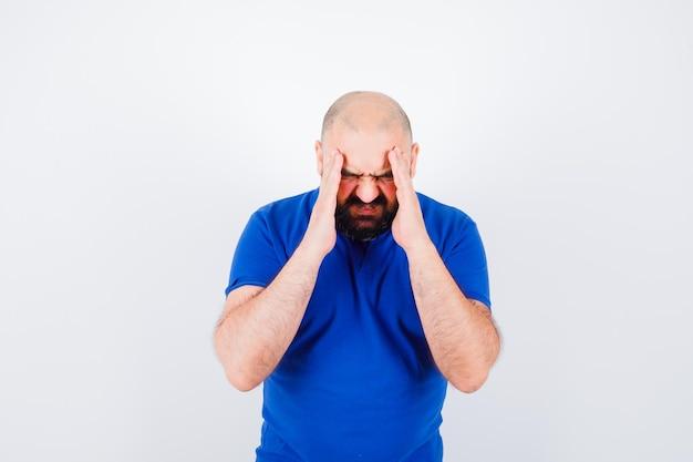 Młody mężczyzna w niebieskiej koszulce ma ból głowy
