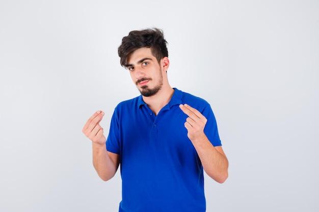 Młody mężczyzna w niebieskiej koszulce pokazujący gest pieniędzy i wyglądający poważnie