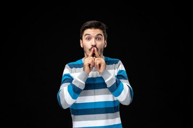Młody mężczyzna w niebieskiej koszulce w paski robi gest ciszy palcami na ustach