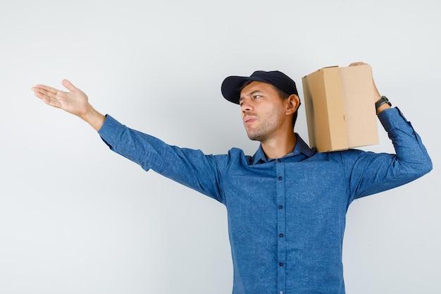 Młody mężczyzna w niebieskiej koszuli, czapka trzymająca karton, krzycząc do kogoś, widok z przodu.