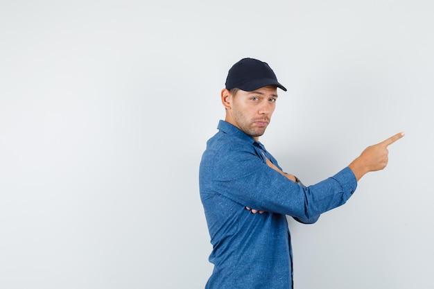 Młody mężczyzna w niebieskiej koszuli, czapka wskazująca i patrząca z powątpiewaniem.