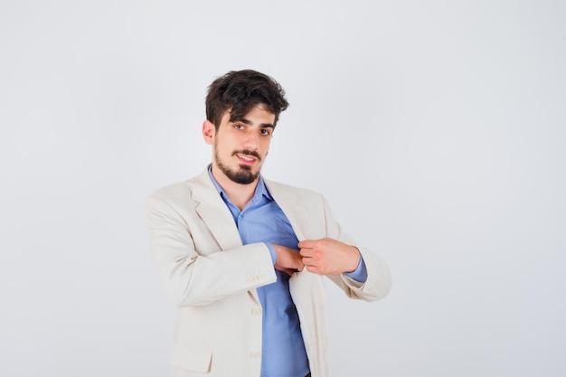 Młody mężczyzna w niebieskiej koszuli i białej marynarce wkłada coś do kieszeni kurtki i wygląda na szczęśliwego
