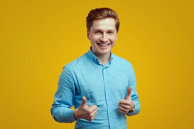 Młody mężczyzna w niebieskiej koszuli pokazujący kciuk nad żółtą ścianą