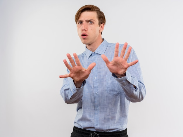 Młody mężczyzna w niebieskiej koszuli robi gest obrony, trzymając się za ręce, nie zbliżając się stojąc nad białą ścianą