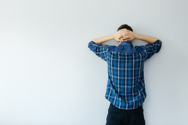Młody mężczyzna w niebieskiej koszuli stoi twarzą do ściany. depresja, problemy i stres