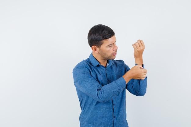 Młody mężczyzna w niebieskiej koszuli zapinany na guziki na rękawie koszuli i patrząc uważnie z przodu.