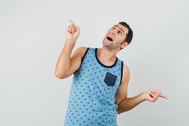 Młody mężczyzna w niebieskim podkoszulku, wskazując palcami w górę iw dół i patrząc z nadzieją