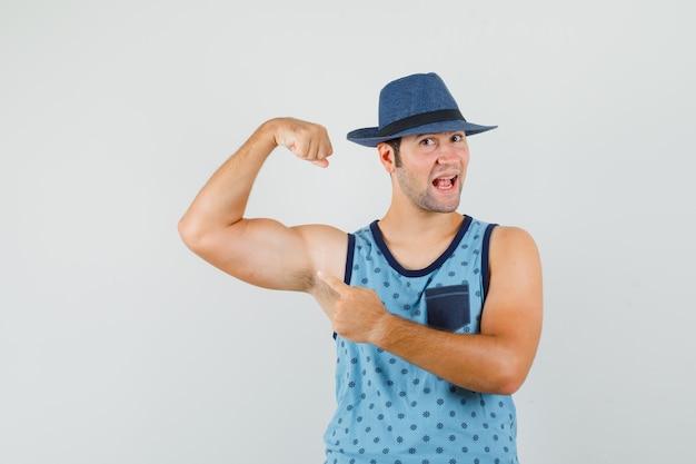 Młody mężczyzna w niebieskim podkoszulku, z kapeluszem wskazującym na mięśnie ramion i wyglądający na silnego