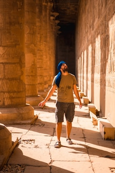 Młody mężczyzna w niebieskim turbanie chodzący po kolumnach świątyni edfu w pobliżu miasta asuan. egipt