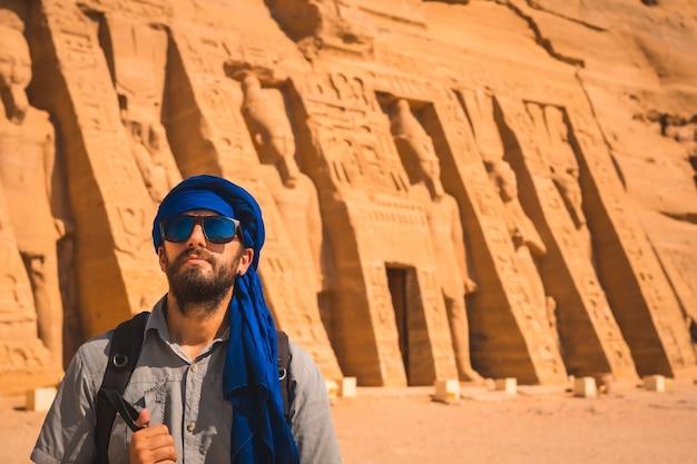 Młody mężczyzna w niebieskim turbanie i okularach przeciwsłonecznych w świątyni nefertari niedaleko abu simbel w południowym egipcie w nubii nad jeziorem naser. świątynia faraona ramzesa ii, podróżniczy styl życia