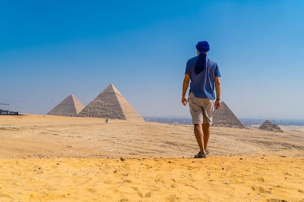 Młody mężczyzna w niebieskim turbanie idący obok piramid w gizie, najstarszego pomnika grobowego na świecie. w mieście kair w egipcie