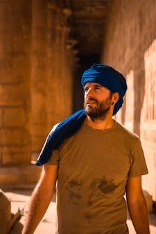 Młody mężczyzna w niebieskim turbanie odwiedza świątynię edfu i jej piękne kolumny w pobliżu miasta asuan. egipt