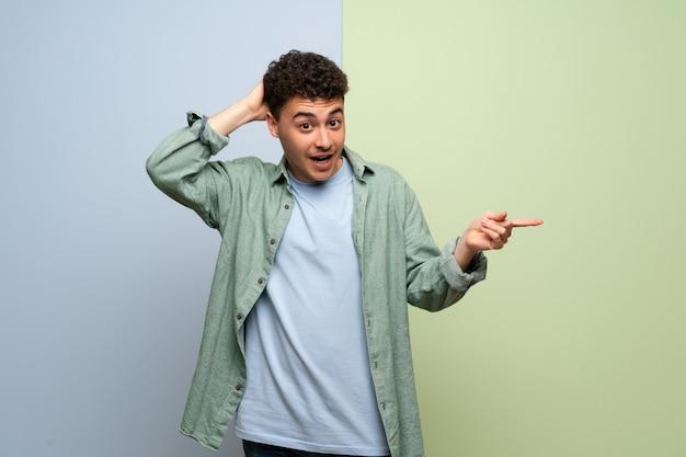 Młody mężczyzna w niebiesko-zielony palec wskazujący z boku i przedstawiający produkt