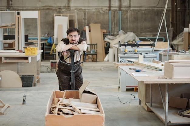Młody mężczyzna w odzieży roboczej i okularach, opierając się na rączce wózka z resztkami podczas przenoszenia ich do warsztatu obróbki
