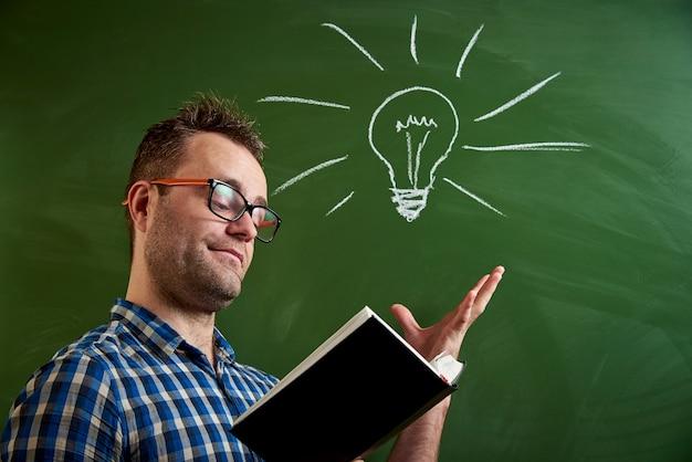 Młody mężczyzna w okularach czyta książkę, przychodzi na myśl pomysł