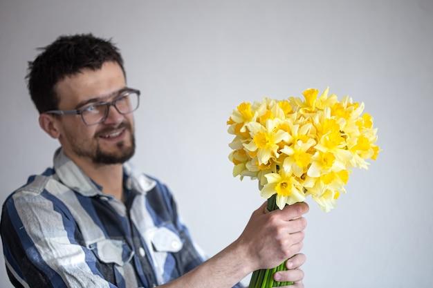 Młody mężczyzna w okularach i koszuli z bukietem żonkili. pojęcie pozdrowienia i dzień kobiet.