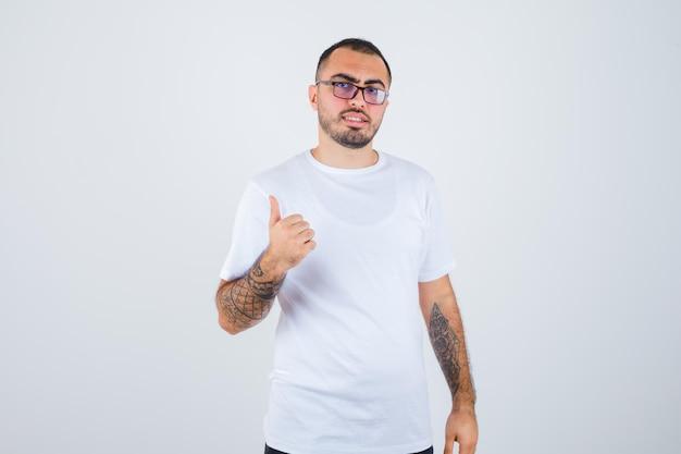 Młody mężczyzna w okularach i pokazujący kciuk w białej koszulce i czarnych spodniach i wyglądający na szczęśliwego