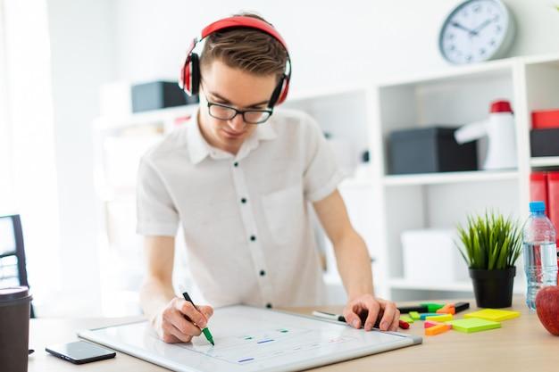 Młody mężczyzna w okularach i słuchawkach rysuje znacznik na tablicy magnetycznej.