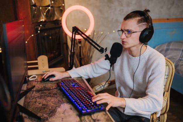 Młody mężczyzna w okularach nagrywa dźwięk podcastu w domu. mężczyzna przy użyciu komputera i dwóch profesjonalistów