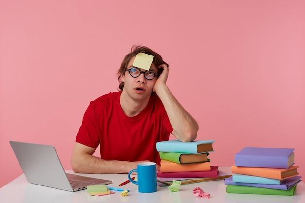 Młody mężczyzna w okularach nosi czerwoną koszulkę, siedzi przy stole i pracuje z notatnikiem i książkami, z naklejką na czole, patrzy w górę i myśli, odizolowane na różowym tle.
