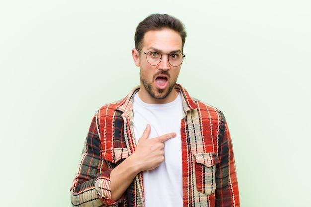 Młody mężczyzna w okularach pozuje, patrząc zszokowany z szeroko otwartymi ustami i wskazując na siebie